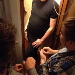 Kolme ihmistä yrittää mahtua pieneen syövytyshuoneeseen